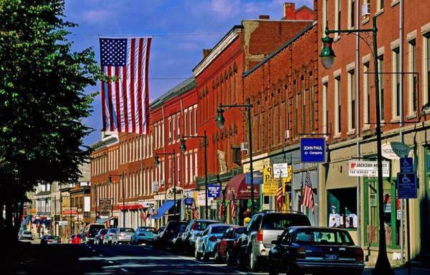 Vintage buildings and American flags line Main Street in picturesque Rockland, Maine.