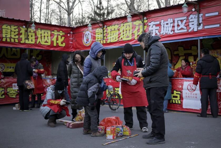 En esta imagen, gente comprando fuegos artificiales para el año nuevo chino en una tienda de Beijing. Buena parte de la población china puede contar con que será difícil dormir cuando comiencen las celebraciones pirotécnicas por el nuevo Año del Mono. (AP Foto/Andy Wong)