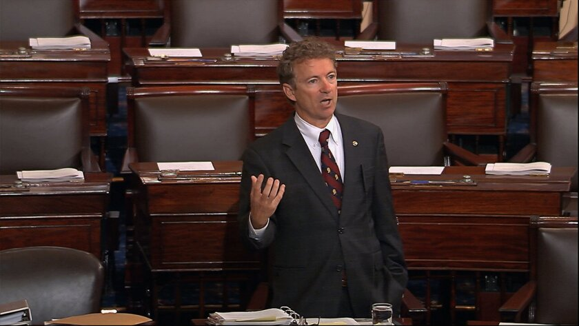 Sen. Rand Paul (R-Ky.) stands at his Senate desk on May 20 before a mostly empty chamber to speak out against a National Security Agency spying program. He held the floor for more than 10 hours.