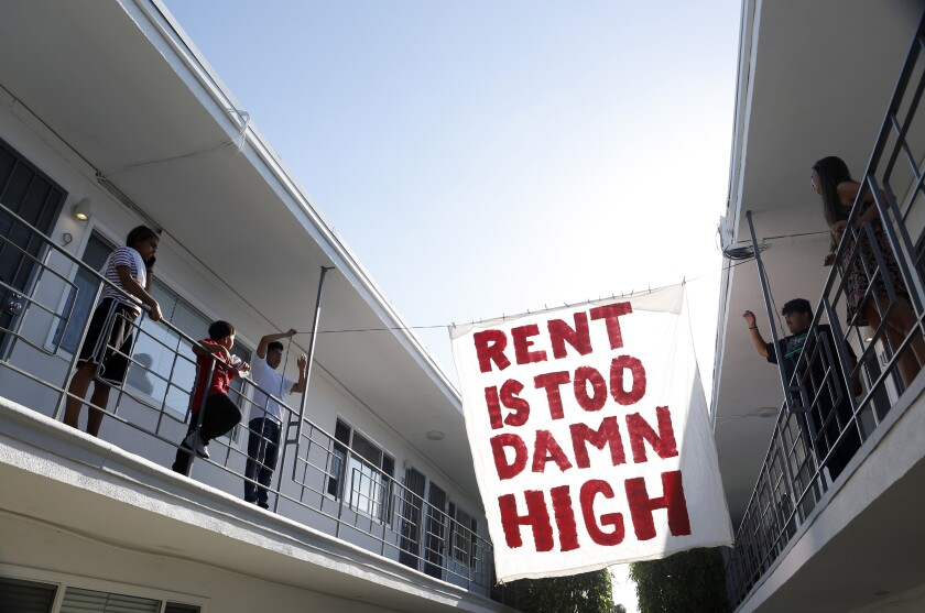 """Organizers with a sign that says, """"Rent is too damn high."""""""