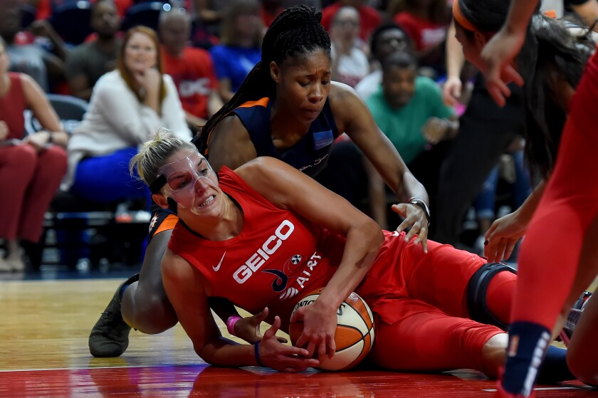 Washington's Elena Delle Donne, bottom, battles Connecticut's Jonquel Jones for the ball during the first half of Game 1 of the WNBA Finals on Sunday.