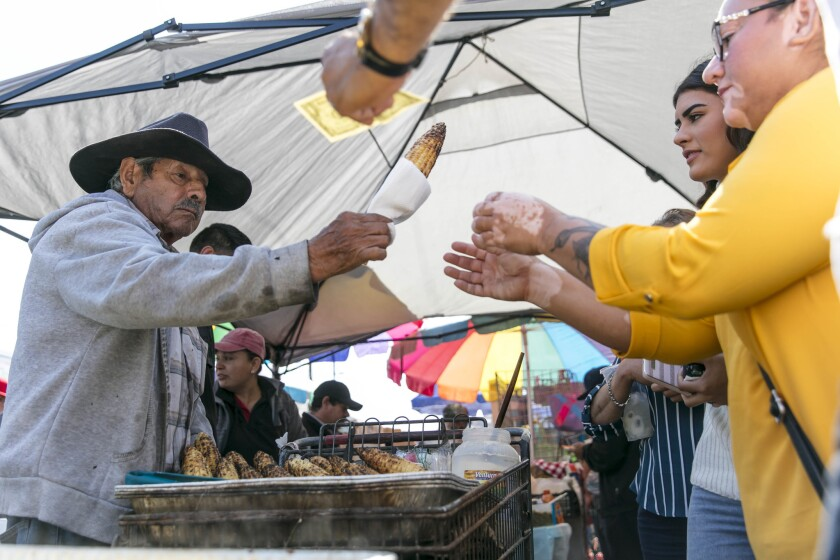 Candelario Padilla, 85, sells roasted corn, one of the favorite offerings at the Piñata District street food market in downtown Los Angeles.