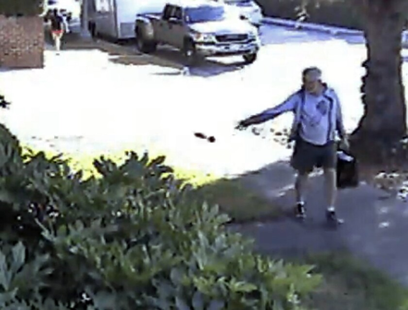 In this June 7 image from a security video provided by Philip Lao, Dennis Kneier, the mayor of San Marino, Calif., tosses a bag of dog waste onto the property of his neighbor, Philip Lao, in San Marino.