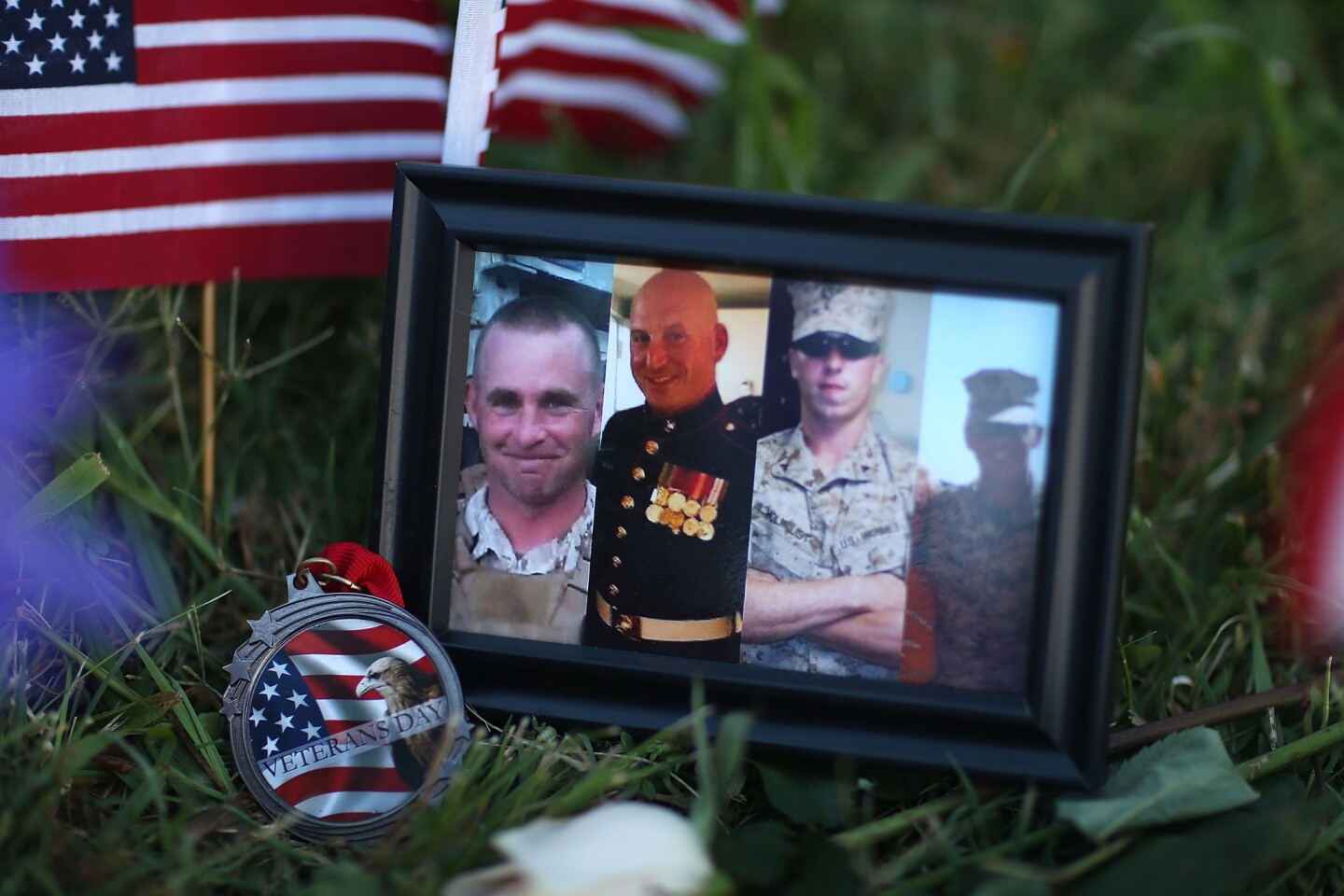 Photos of four slain Marines are placed at a makeshift memorial at a military recruiting center in Chattanooga, one of two military centers a gunman targeted. A fifth victim, a Navy sailor, has also died.