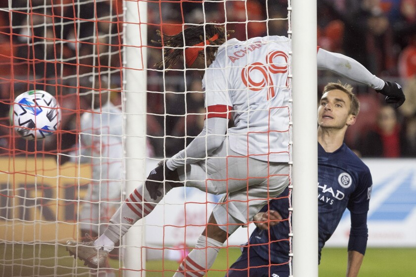 Toronto FC forward Ifunanyachi Achara (99) heads his team's game winning goal as New York City FC midfielder James Sands (16) looks on during the second half of an MLS soccer game in Toronto, Saturday March 7, 2020. (Chris Young/The Canadian Press via AP)
