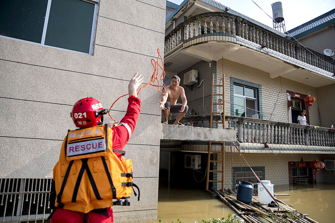 A rescue volunteer throws a rope to a resident in Poyang.