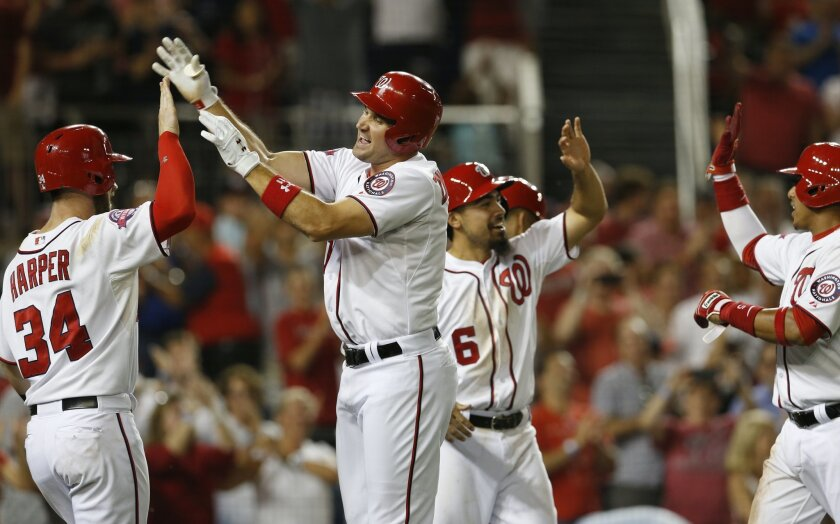 Washington Nationals' Ryan Zimmerman, second from left, celebrates hitting a grand slam with teammates Bryce Harper (34), Anthony Rendon (6) and Yunel Escobar during the sixth inning of a baseball game against the San Diego Padres at Nationals Park, Tuesday, Aug. 25, 2015, in Washington. (AP Photo/Carolyn Kaster)