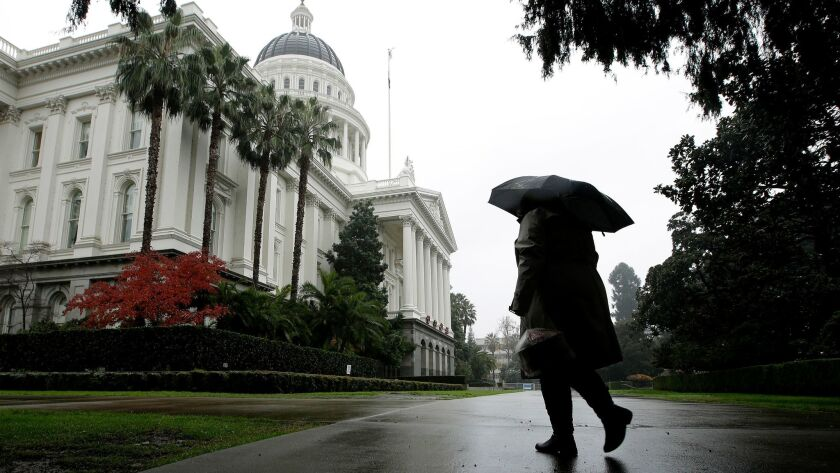 Umbrellas were put to use as a storm passes over the state Capitol in Sacramento, Calif., Thursday,