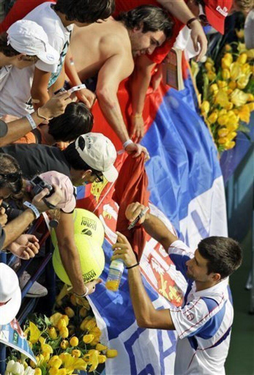 Serbia's Novak Djokovic signs autographs after defeating Tomas Berdych of Czech Republic during their semifinal tennis match at the Dubai ATP Tennis Championships in Dubai, United Arab Emirates, Friday, Feb. 25, 2011. (AP Photo/Kamran Jebreili)