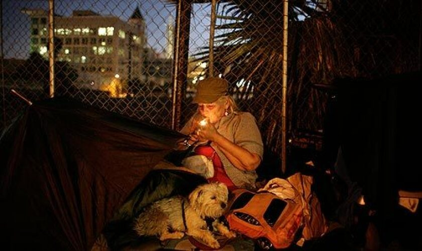"""Joanna Said settles in with her dog, Jackie Onassis, and lights up a last cigarette before going to sleep along a Hollywood street. She said she's 67 and has little hope of putting her life back on track. """"I'm one of the people who should not be homeless,"""" she said. """"Who's going to hire me to do anything?"""" More photos >>>"""