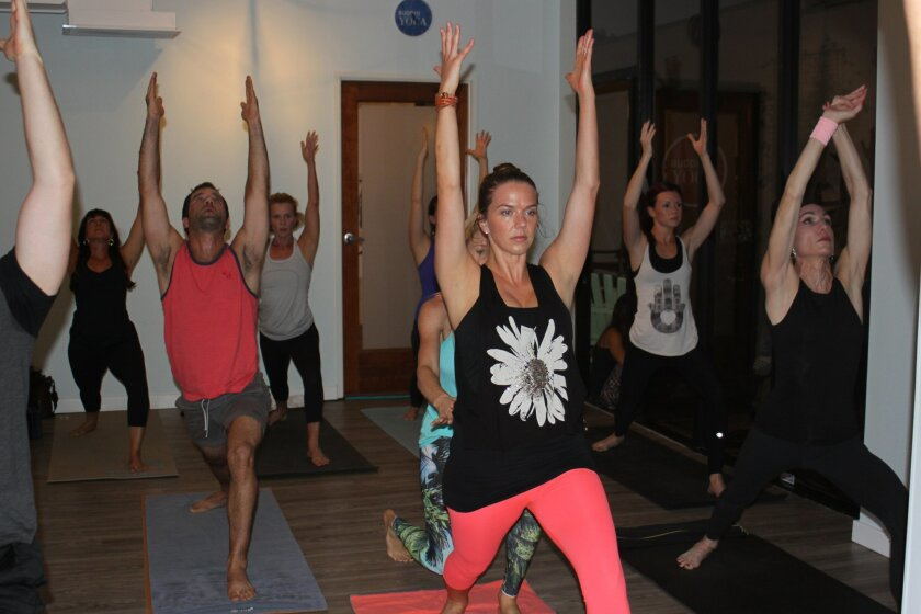 At Buddhi Yoga's Nov. 7 opening on Girard Avenue, yogis of all skill levels participate in a community class.
