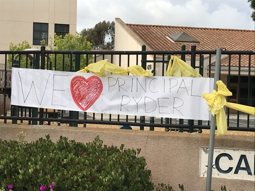 Signs on the school and throughout the neighborhood call for the return of Carmel Creek Principal Lisa Ryder.