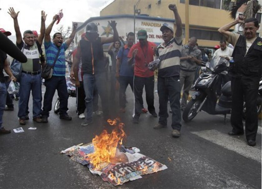 "Government ""Chavista"" supporters burn an election poster of opposition presidential candidate Henrique Capriles in Los Teques, on the outskirts of Caracas, Venezuela, Tuesday, April 16, 2013.  President-elect Nicolas Maduro is blaming Capriles for seven deaths that the government says occurred in p"
