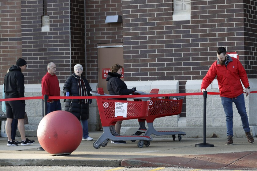 Grocery services are in high demand. Above, people wait to enter a Target store last month in Glenview, Ill.