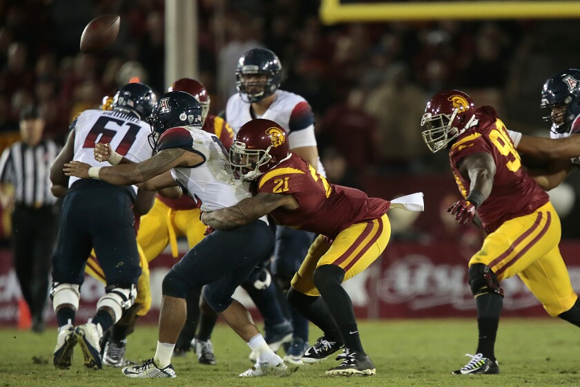 USC linebacker Su'a Cravens causes Arizona quarterback Anu Solomon to fumble during the fourth quarter of the Trojans' 38-30 win over the Wildcats last Saturday.