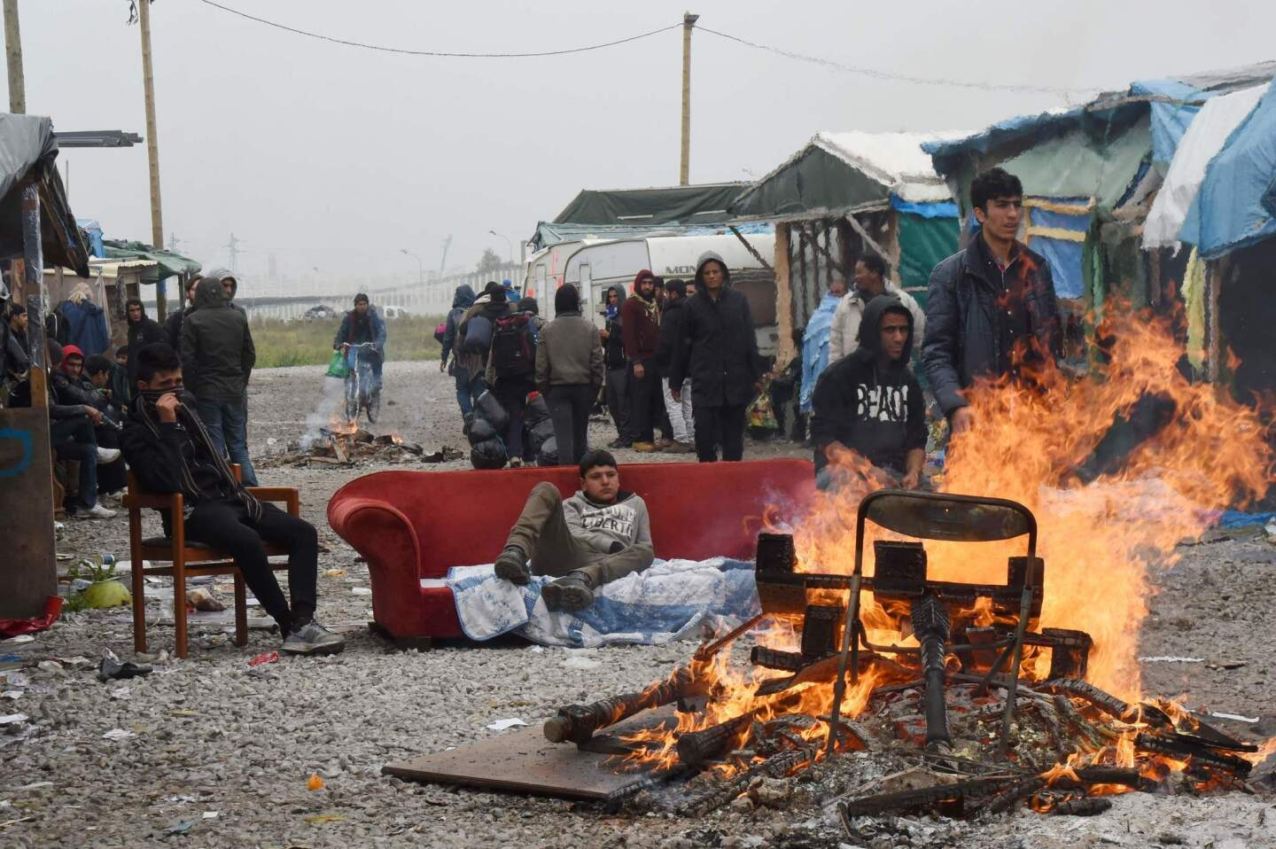 """Migrants gather by their tents and a bonfire in a migrant camp known as """"the Jungle,"""" in Calais, France, before an operation to clear the camp of its estimated 6,000 to 8,000 occupants."""