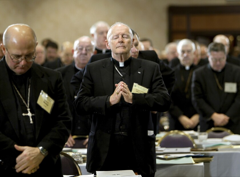 Then-Cardinal Theodore Edgar McCarrick, standing among other priests, closes his eyes and holds his hands in prayer.