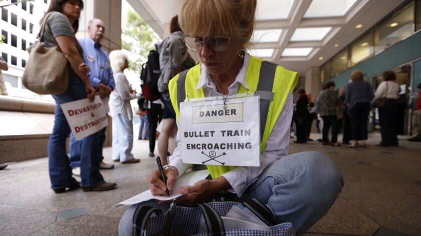 Even before an exact route for the bullet train has been chosen, Californians are protesting its impact. Above, Shannon McGinnis joins a 2015 protest at a California High-Speed Rail Authority meeting in downtown L.A.
