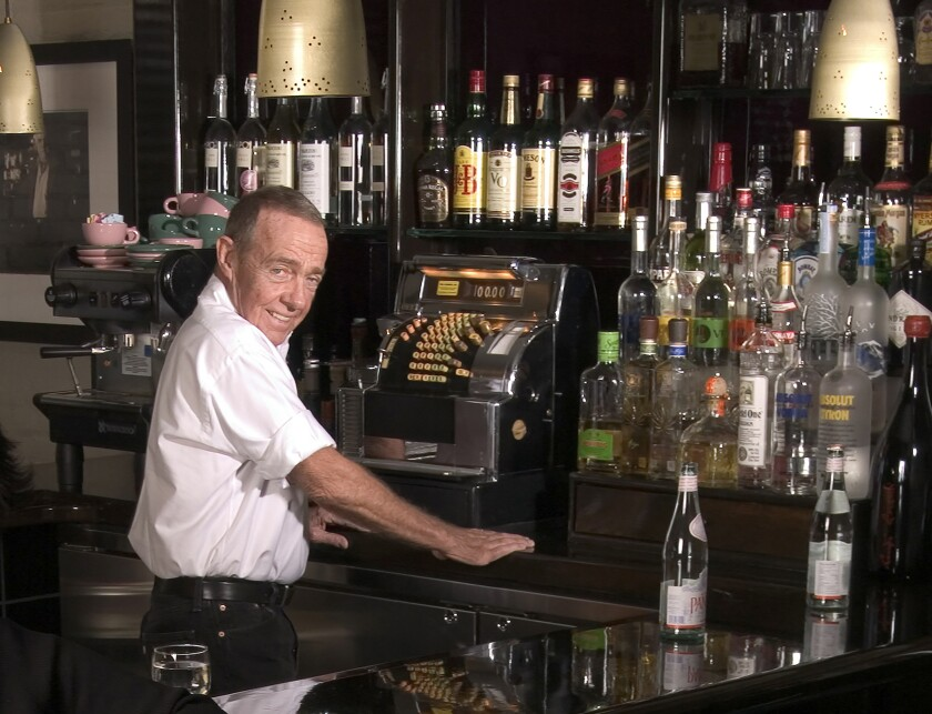 FILE - Joe Allen, proprietor of Joe Allen's restaurant poses behind the bar in New York on Nov. 10, 2005. Allen, whose Times Square-adjacent bistro which bears his name has been a decades-long draw for theater folk and where a post-Broadway drink is part of the Broadway experience, has died. He was 87. Allen died Sunday, Feb. 7, 2021, in Hampton, New Hampshire, according to Jason Woodruff, a former staffer for the Allen family of restaurants who spoke to the family. (AP Photo/Jim Cooper, File)