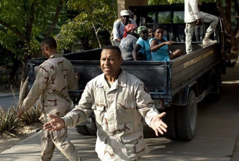 In this photo taken on Jan. 29, 2011, a Dominican specialized military border officer tells reporters not to document a group of detained Haitians, seen in the bed of truck, in Jimani, Dominican Republic. The largest campaign in years to deport Haitians living illegally in the Dominican Republic is