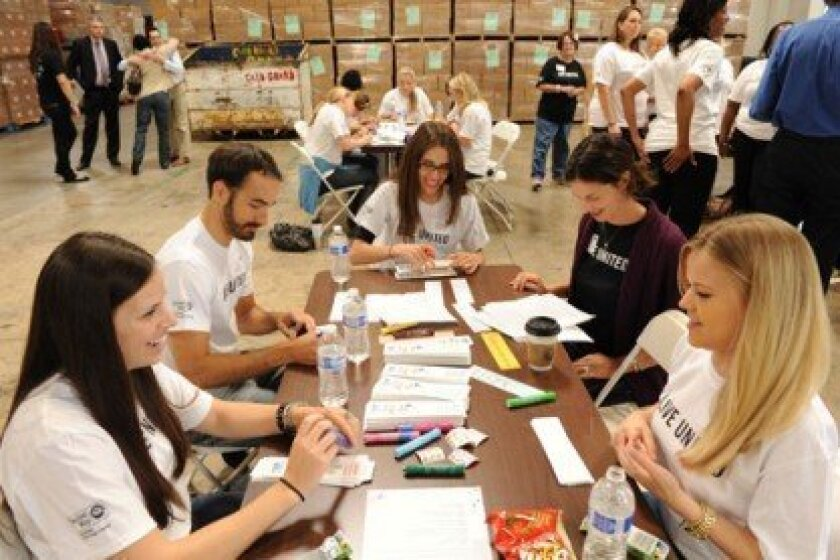 For United Way's Day of Action 2013 in June, corporate volunteers helped fund and assemble 25,000 bilingual summer book kits for low-income children. Photo/United Way of San Diego County