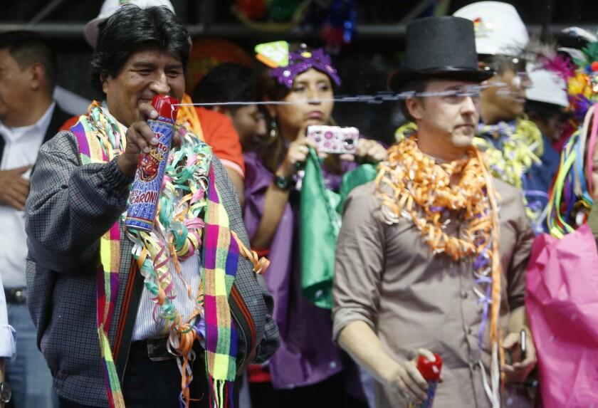 El presidente boliviano Evo Morales lanza espuma en los festejos de Carnaval frente al palacio de gobierno en La Paz, Bolivia. (AP Foto/Juan Karita)