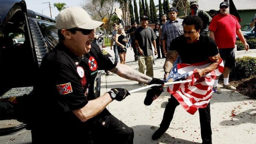 Un hombre del Ku Klux Klan (izq.) pelea contra un manifestante por una bandera de los EE.UU., luego de que miembros del KKK intentaran realizar una marcha en Pearson Park, Anaheim, en febrero pasado. Siete de los manifestantes fueron ahora acusados de atacar a los miembros del Klan.