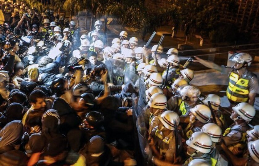 Demonstrators clash with the riot police in front of the legislative assembly in Sao Paulo as they demand the resignation of officials over the disappearance of construction worker Amarildo de Souza.