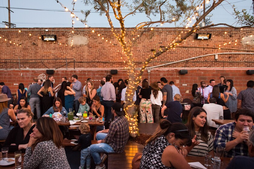 Patrons fill the outdoor patio at Everson Royce Bar