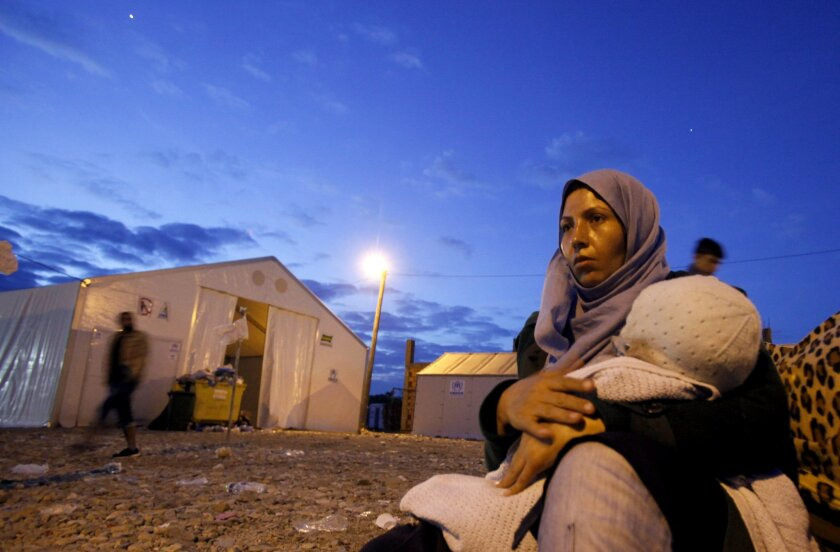 A refugee woman holds a baby while waiting for a train towards Serbia, at the transit camp for refugees near the southern Macedonian town of Gevgelija, after crossing the border from Greece, Friday at dawn, Oct. 2, 2015. The international Red Cross says vulnerable migrants in the Balkans are facing