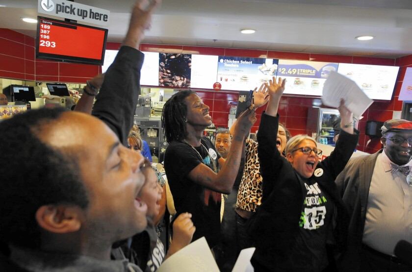 Workers protest McDonald's decision to raise its minimum wage, saying it should also include employees at franchised stores.