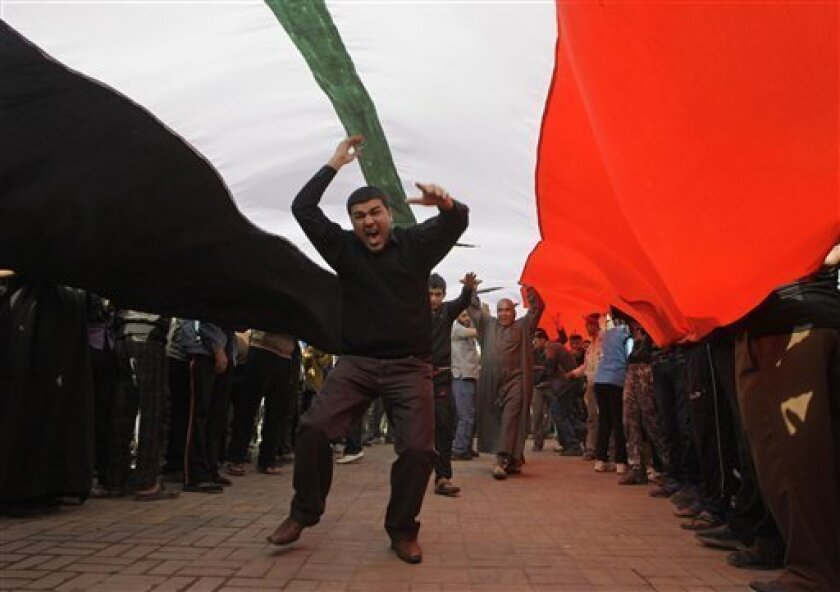 FILE - In this Feb. 23, 2011 file photo, protesters chant anti-Iraqi government slogans under a huge Iraqi flag during a protest at Tahrir Square in Baghdad, Iraq. A leading human rights group says Iraq's central government and regional Kurdish leaders are beating and illegally detaining protesters to try to stop demonstrations calling for reforms. The New York-based Human Rights Watch called on Iraqi authorities on Thursday, June 2, 2011 to release detained protesters or formally charge those suspected of breaking the law. (AP Photo/Khalid Mohammed, File)