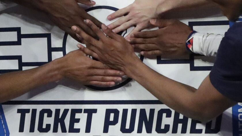 Villanova players stick a logo of their team on a bracket board after defeating Seton Hall 74-72 in