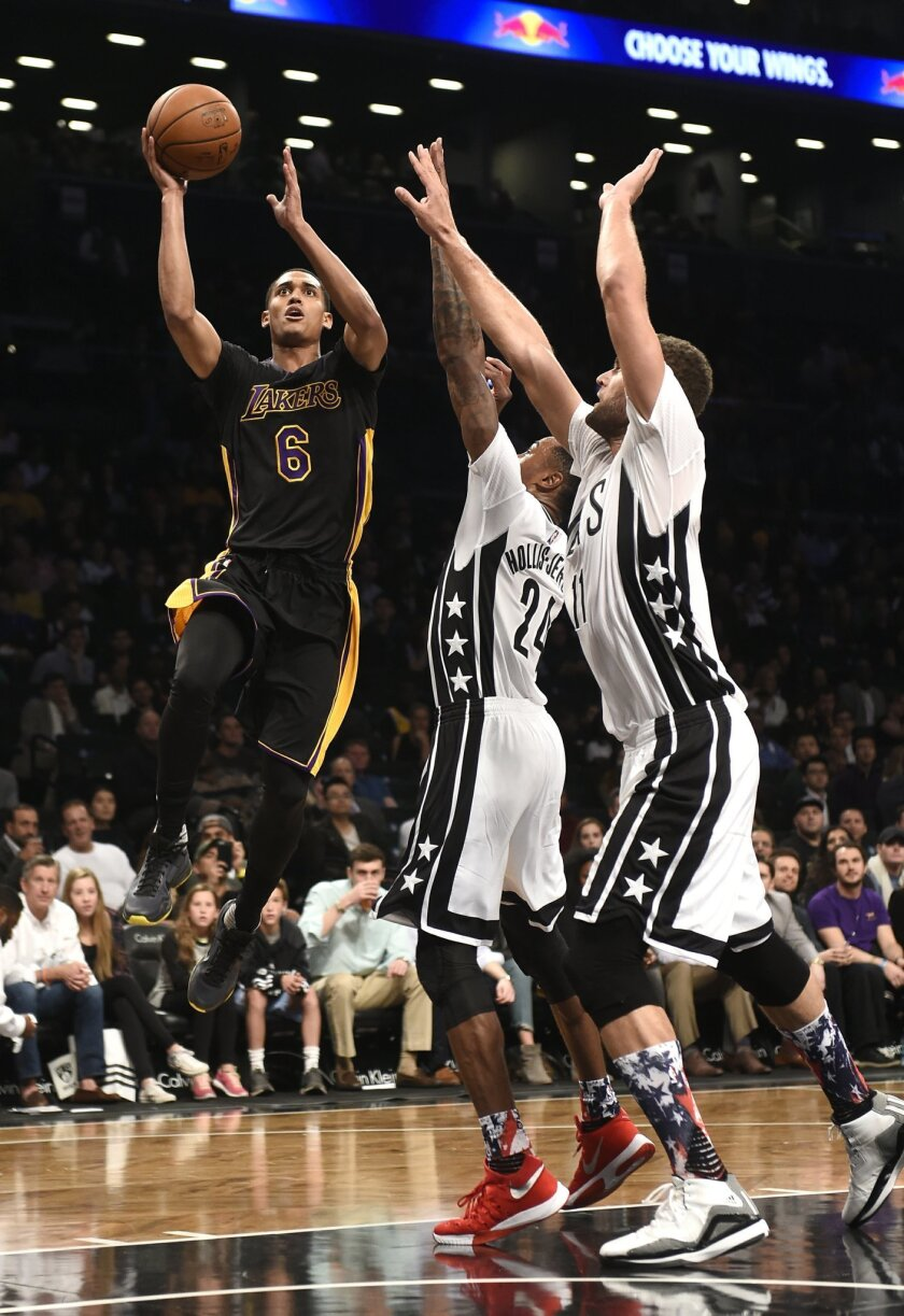 Los Angeles Lakers guard Jordan Clarkson (6) drives the ball to the basket against Brooklyn Nets forward Rondae Hollis-Jefferson (24) and center Brook Lopez (11) during the first half of an NBA basketball game Friday, Nov. 6, 2015, in New York. (AP Photo/Kathy Kmonicek)