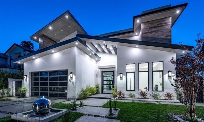 The two-story home expands to a patio with a waterfall and a backyard with a pool and custom dog house.