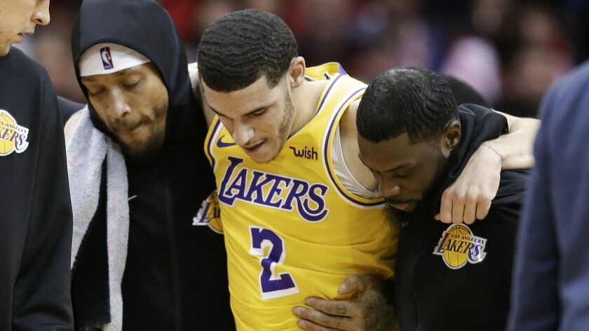 Lakers guard Lonzo Ball is carried off the court by Michael Beasley, left, and Lance Stephenson after Ball sustained an injury during the second half against the Houston Rockets on Saturday.