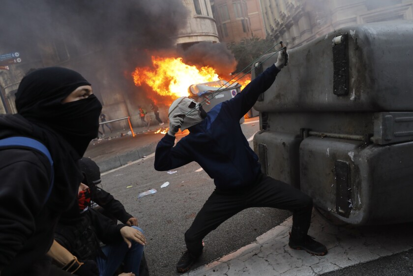 A protester uses a slingshot during clashes with police in Barcelona, Spain