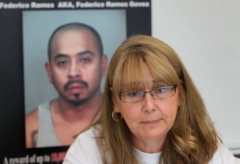 Debbie, the mother of shooting victim Daniel Alexander, speaks in front of a large photo of her son's suspected killer, Federico Ramos. Police say Ramos shot Alexander, unprovoked, in Escondido on July 4, 2009. Ramos has evaded capture. Debbie, who spoke at the police headquarters Wednesday, did not want her last name used for fear of retribution.