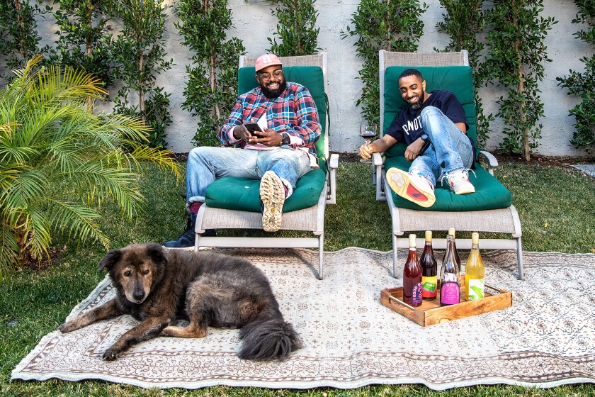 Teron Stevenson, left, and Khalil Kinsey, two of the cofounders of Natural Action Wine Club, on lounge chairs with a dog.