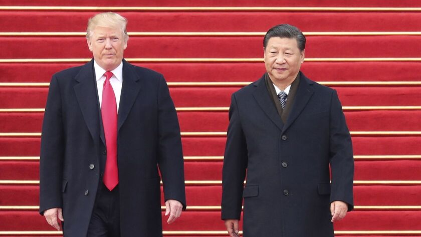 Chinese President Xi Jinping, right, welcomes President Donald Trump at the square outside the east gate of the Great Hall of the People in Beijing on Nov. 9, 2017.