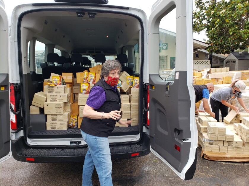 RCHS President Judi Sanzo putting the last boxes of food into a van.