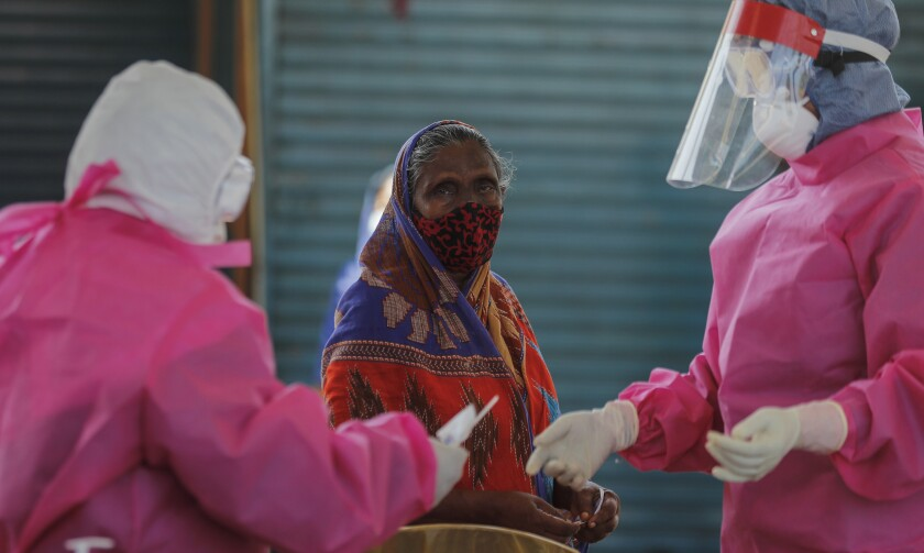 A Sri Lankan woman prepares to give swab samples to test for COVID-19 in Colombo, Sri Lanka, Monday, Nov. 9, 2020. Sri Lanka is in the midst of a new wave originating from a garment factory and the country's main wholesale fish market, where the number of infected and deaths are increasing. (AP Photo/Eranga Jayawardena)