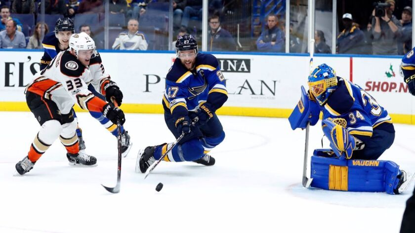 Ducks' Jakob Silfverberg and St. Louis Blues' Alex Pietrangelo, center, reach for a loose puck as Blues goalie Jake Allen, right, defends during the first period on Wednesday.