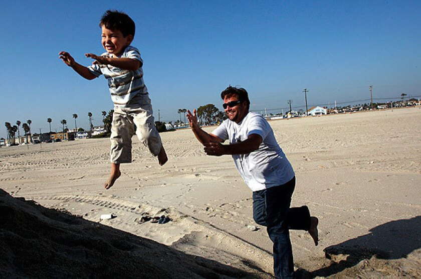 Joe Mozingo plays with his son Blake, 4, at Belmont Shore in Long Beach. He wants his children to know about their ancestry.
