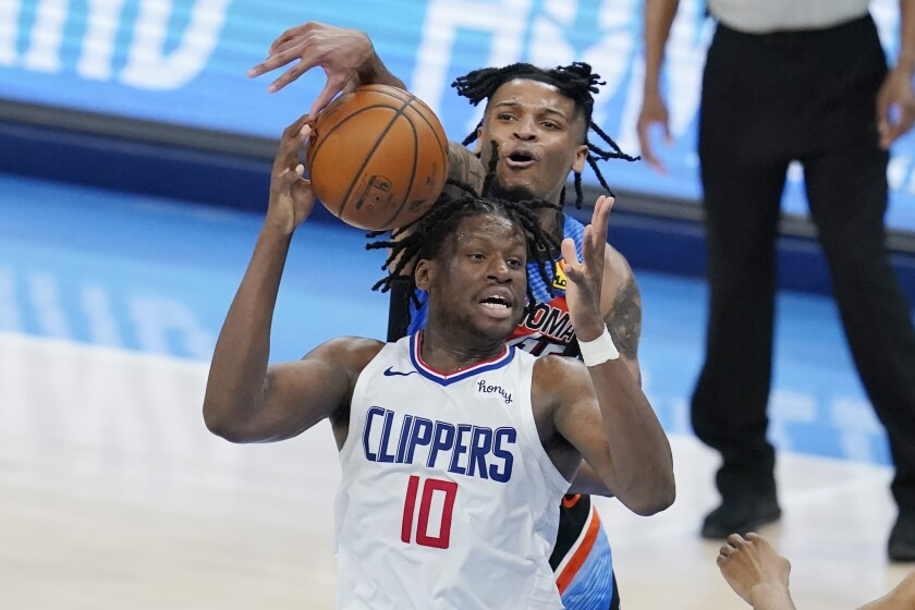 Oklahoma City Thunder forward Josh Hall tries to knock the ball away from Clippers center Daniel Oturu.