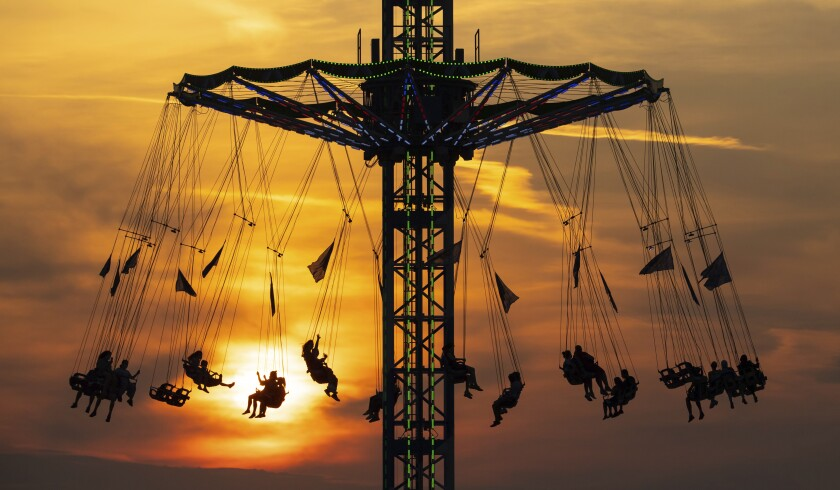 Numerous people ride a chain carousel in the Olympic Park in Munich, Germany, during sunset Wednesday Aug. 12, 2020. (Sven Hoppe/dpa via AP)