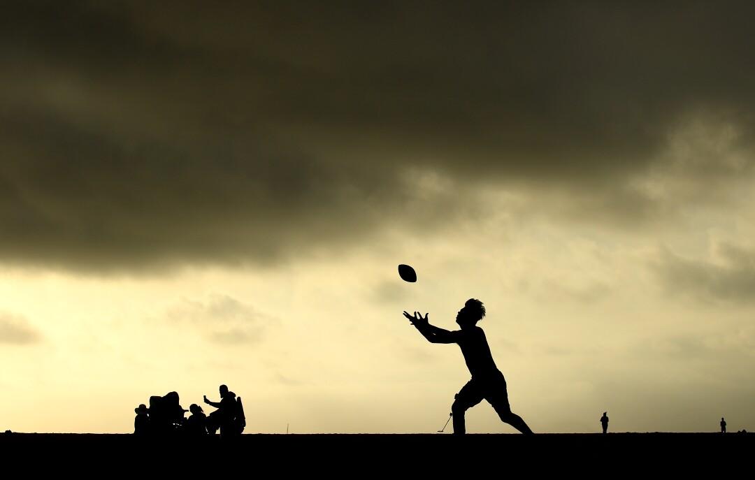 David Ruiz of Compton plays football a Venice Beach on Tuesday.