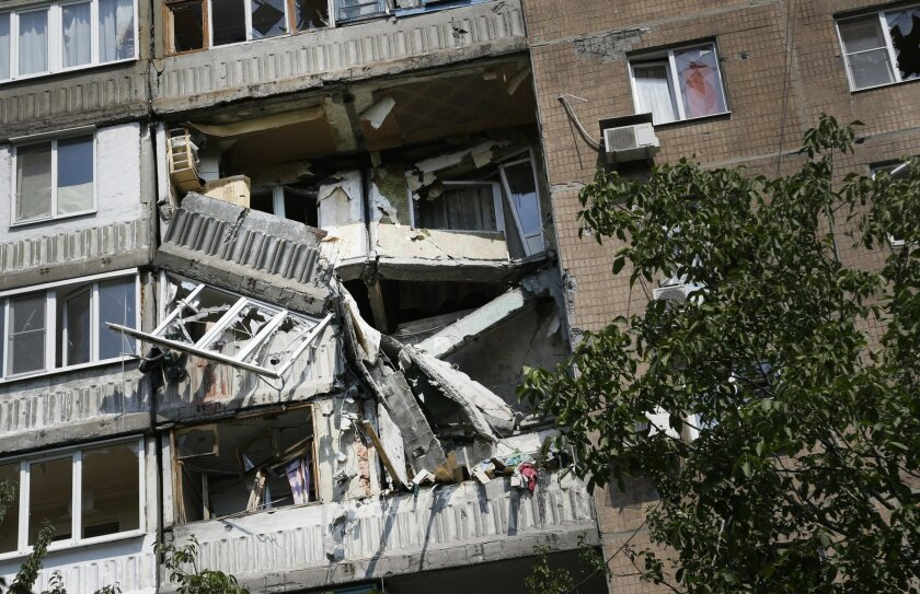 A damaged apartment house is seen after shelling in Donetsk, eastern Ukraine, Wednesday, Aug. 13, 2014. At least three people have been killed in the separatist-controlled city of Donetsk in eastern Ukraine as the government intensifies its shelling campaign. (AP Photo/Sergei Grits)