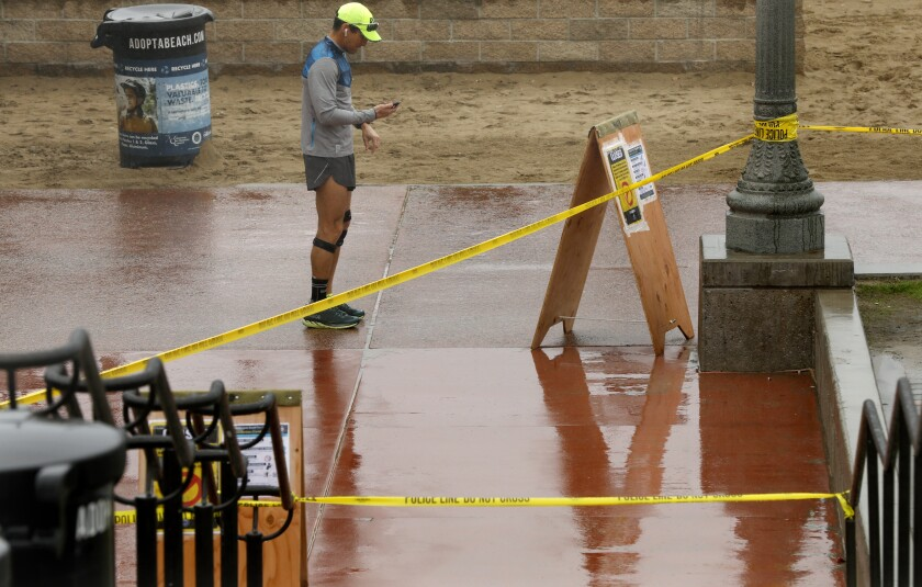 A runner pauses near a taped off staircase leading to the closed Huntington Beach Pier