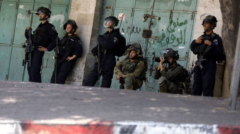 Israeli army soldiers take position during clashes with Palestinian stone throwers in the West Bank city of Hebron on Aug. 10.